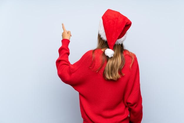 人差し指で戻って指している分離の青い背景上のクリスマス帽子の少女