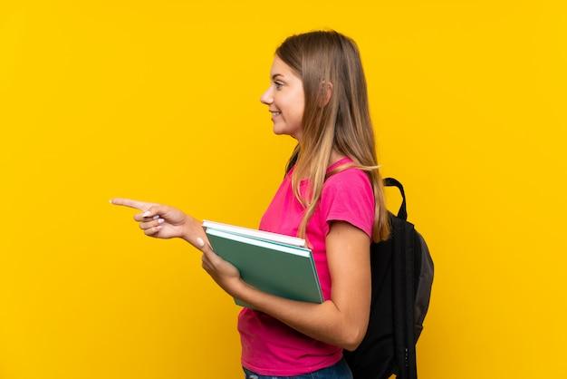 製品を提示する側を指している孤立した黄色の背景の上の若い学生の女の子