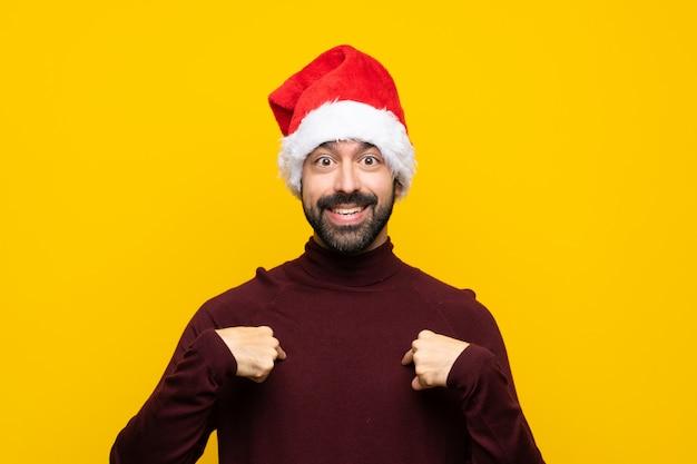 驚きの表情で孤立した黄色の背景上のクリスマス帽子の男