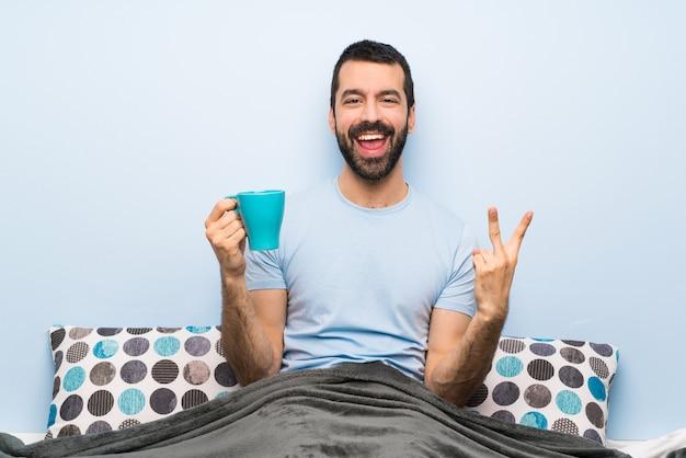 コーヒーのカップを保持しているひげとベッドの男