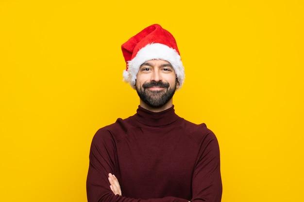 Человек в рождественской шляпе держит руки скрещенными в лобном положении