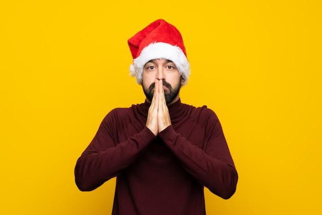 Человек в шляпе рождество держит ладонь вместе. человек просит что-то