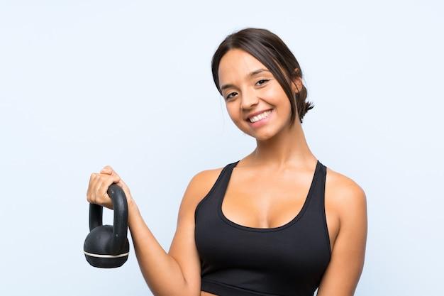 ケトルベルで重量挙げを作る若いスポーツ少女