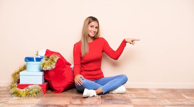 Девушка в рождественские праздники, сидя на полу, указывая пальцем в сторону