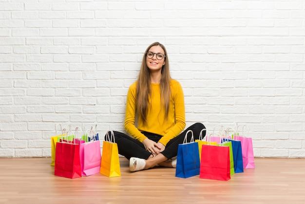 多くのメガネと幸せな買い物袋を持つ少女