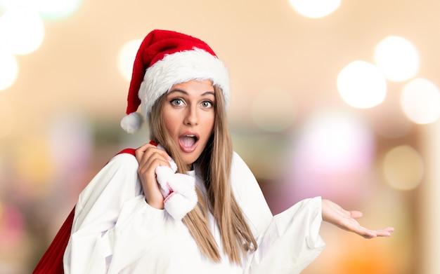 Молодая белокурая женщина, собирающая сумку, полную подарков в рождественские каникулы на несосредоточенном фоне