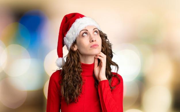 やり場のない背景の上のアイデアを考えてクリスマス帽子の少女