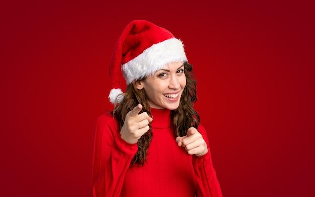 クリスマスの帽子を持つ少女はあなたに指を指す