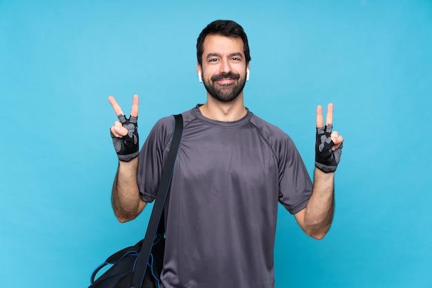 両方の手で勝利のサインを示す分離の青い壁の上のひげを持つ若いスポーツ男