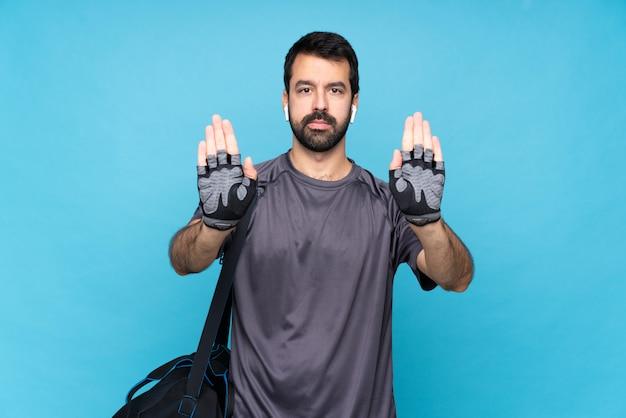 Молодой спортивный человек с бородой над изолированной синей стеной, делая жест остановки и разочарован