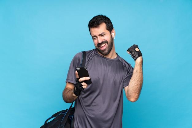 勝利の位置に電話で孤立した青い壁の上のひげを持つ若いスポーツ男