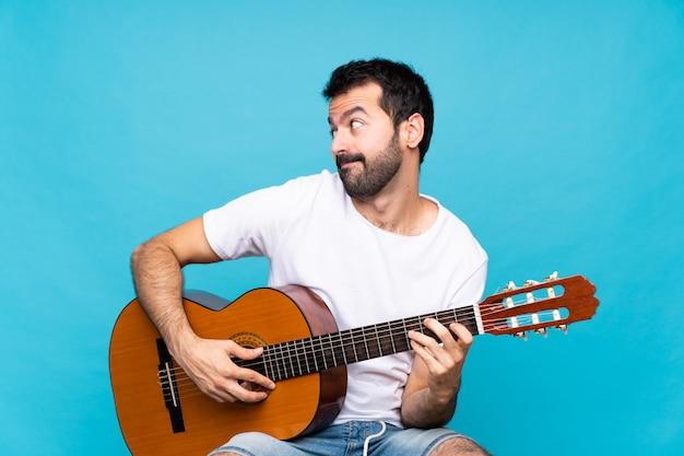 側を探している疑いジェスチャーを作る分離の青い壁の上のギターを持つ若い男
