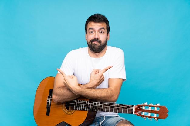 疑問を持つ側面を指している分離の青い壁の上のギターを持つ若い男
