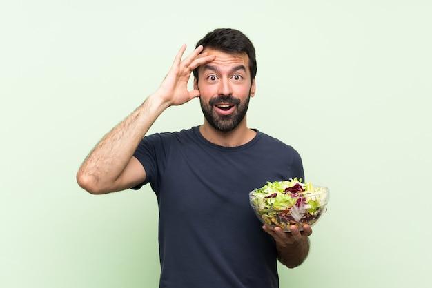 孤立した緑の壁の上のサラダと若いハンサムな男はちょうど何かを実現し、解決策を意図しています