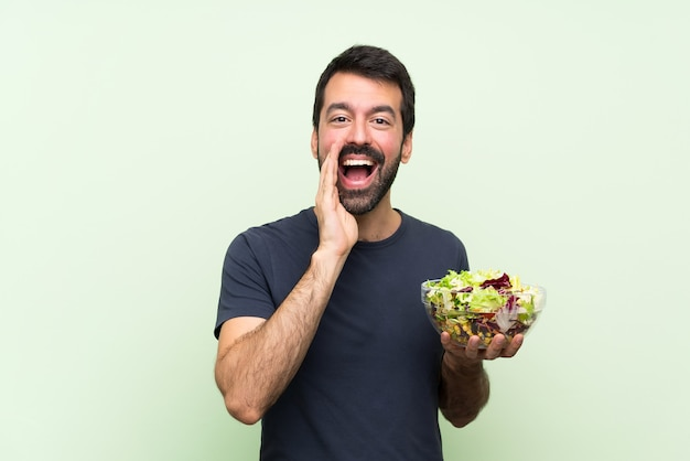 孤立した緑の壁の叫びと何かを発表上のサラダと若いハンサムな男