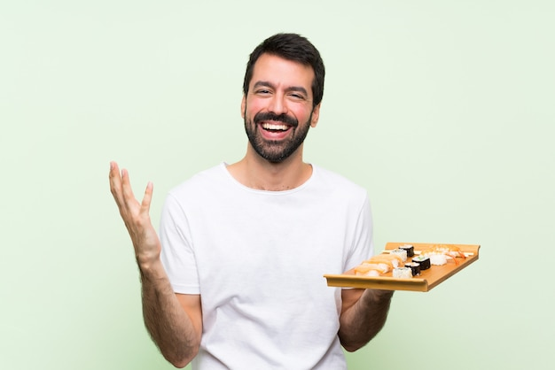 たくさんの笑みを浮かべて孤立した緑の壁の上の寿司と若いハンサムな男