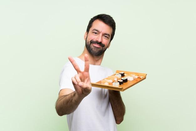 笑顔と勝利のサインを示す分離の緑の壁の上の寿司と若いハンサムな男