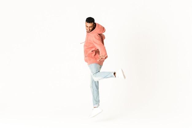Человек танцует уличный танец стиль над изолированной белой стеной