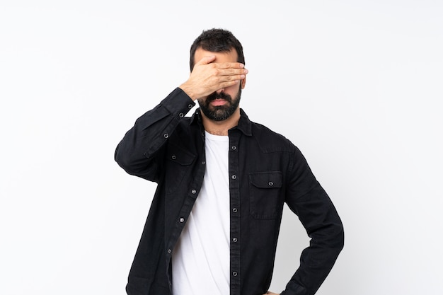 手で目を覆っている孤立した白い壁の上のひげを持つ若者。何かを見たくない