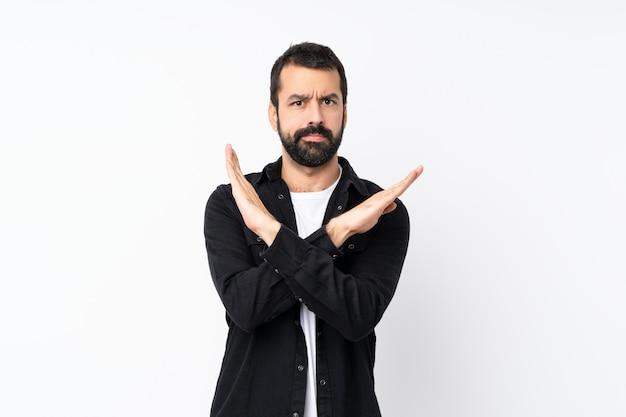 Молодой человек с бородой на изолированной белой стене не делает жест