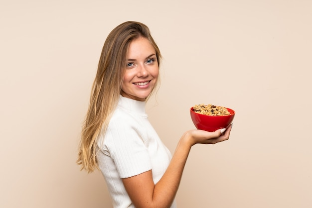 Молодая белокурая женщина над изолированной стеной держа миску хлопьев