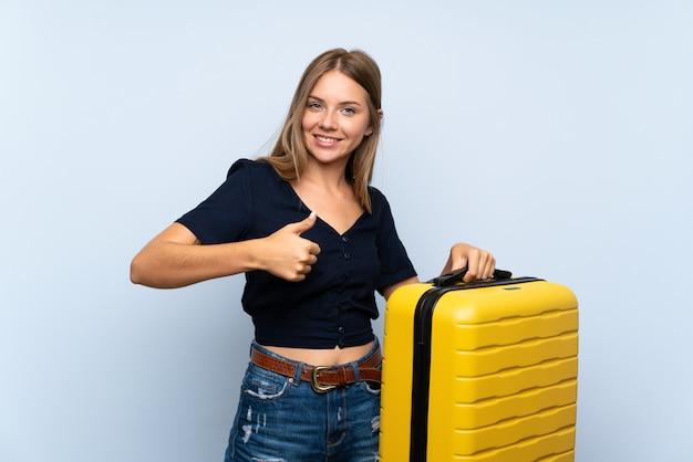 Блондинка путешественница с чемоданом с пальцами вверх, потому что случилось что-то хорошее