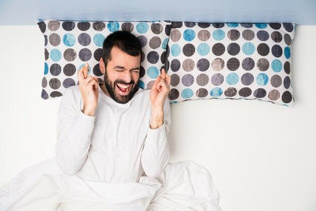 Человек в постели в вид сверху с скрестив пальцы