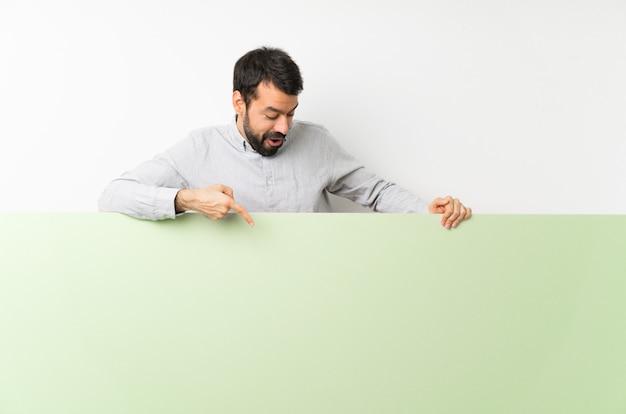 大きな緑の空のプラカードを押しながらそれを指すひげの若いハンサムな男