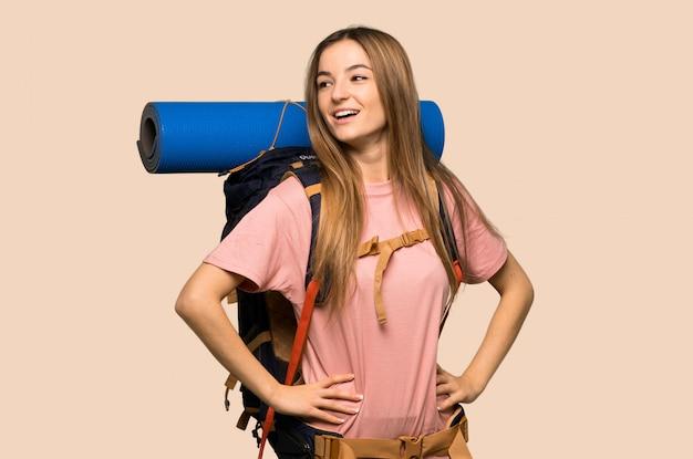 Молодая женщина рюкзаком позирует с руки на бедре и смех на изолированных желтой стене