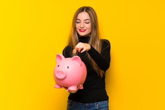 Молодая милая женщина над желтой стеной принимая копилку и счастливая потому что она полна