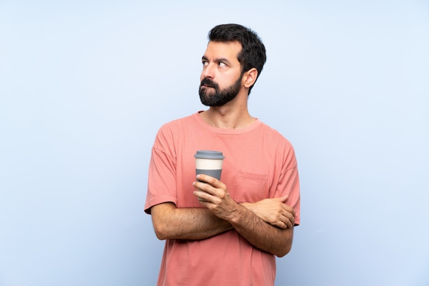 Молодой человек с бородой, держа прочь кофе на изолированной синей стене с выражением лица смутить