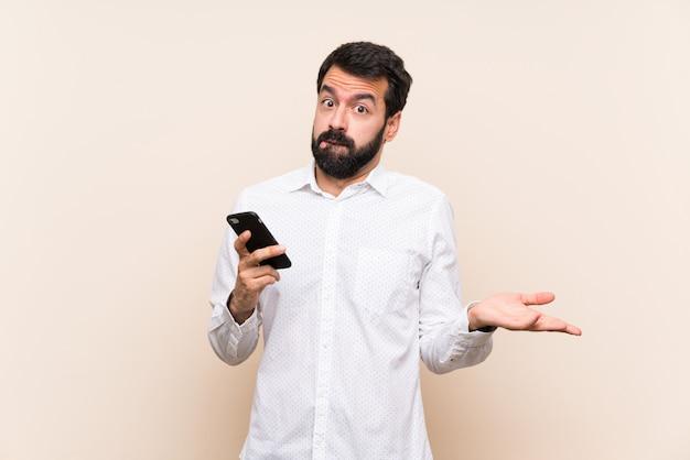 手を上げながら疑問を持つ携帯を保持しているひげを持つ若者