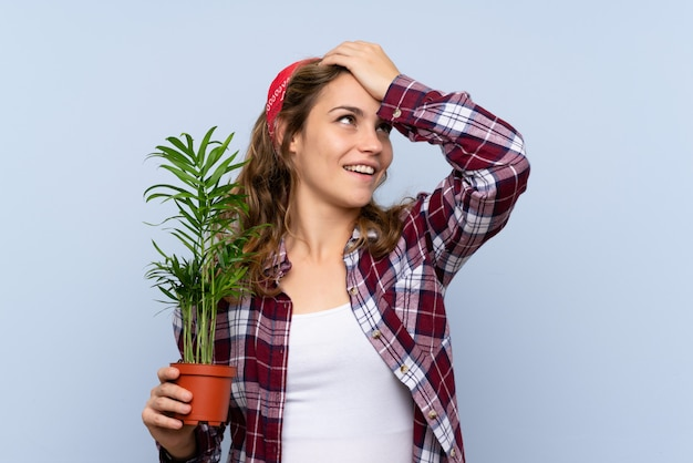 植物を保持している若い金髪の庭師の女の子は何かを実現し、解決策を意図