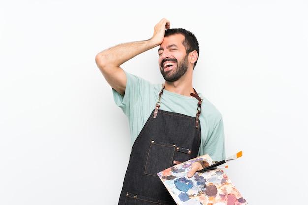 孤立した壁の上にパレットを保持している若いアーティストの男は何かを実現し、解決策を意図しています
