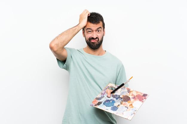 Молодой художник мужчина держит палитру над изолированной стеной с выражением разочарования и непонимания