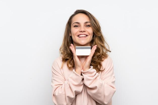 クレジットカードを保持している若いブロンドの女性