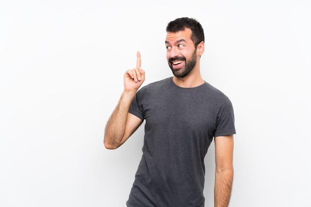 指を持ち上げながら解決策を実現しようとしている孤立した白い壁の上の若いハンサムな男