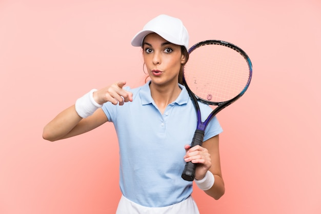 孤立したピンクの壁の上の若いテニスプレーヤー女性驚いて、フロントを指す