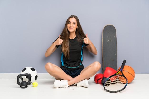 親指ジェスチャーを与える床に座っている若いスポーツ女性