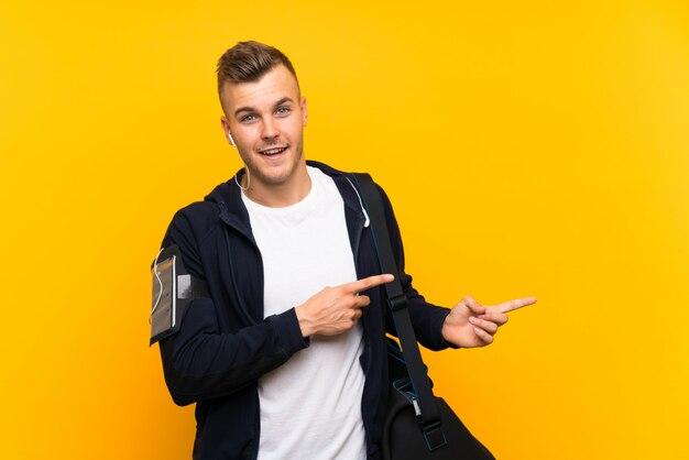孤立した黄色の壁に若い金髪スポーツ男驚いて、ポインティング側