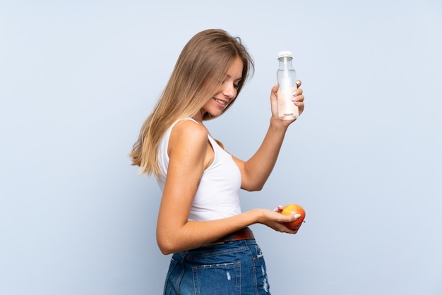 Молодая блондинка с бутылкой воды над изолированной стеной