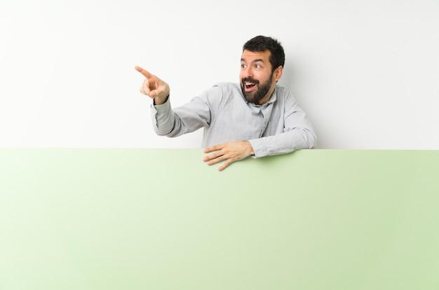 離れて指している大きな緑の空のプラカードを保持しているひげの若いハンサムな男