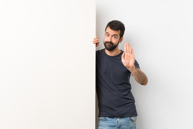 Молодой красавец с бородой, проведение большой пустой плакат, делая остановки жест