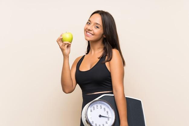 Молодая спортивная девушка с весами над изолированной стеной