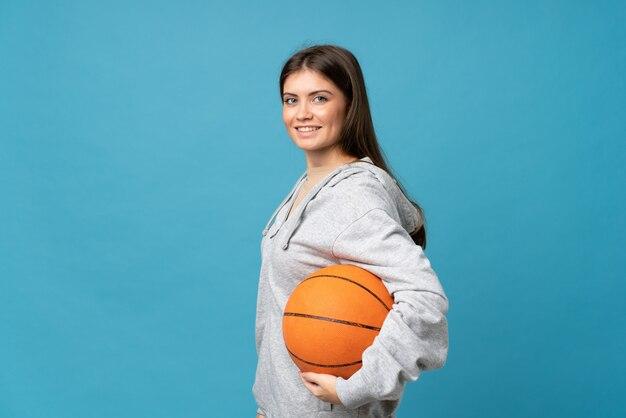 バスケットボールのボールで孤立した青い背景上の若い女性