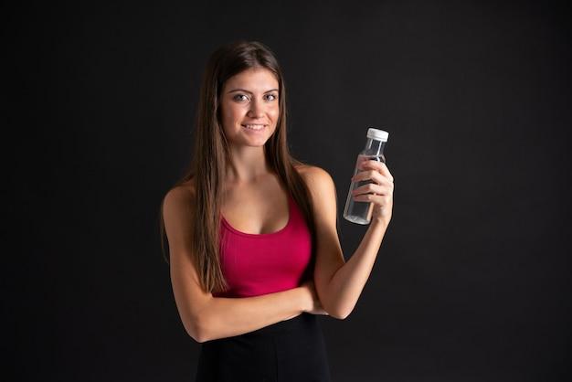 孤立した黒い背景の上の水のボトルを持つ若いスポーツ女性