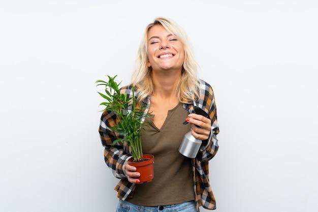 Молодая белокурая женщина садовника держа завод моча его над изолированной белой предпосылкой