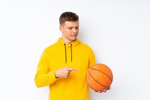バスケットボールのボールとそれを指している分離の白い背景の上の若いハンサムな男
