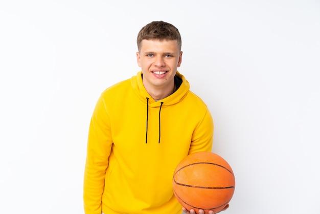 バスケットボールのボールで孤立した白い背景の上の若いハンサムな男