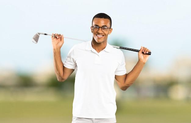 屋外でアフロアメリカンゴルファープレーヤー男